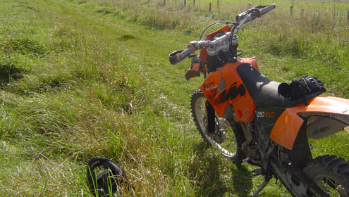 Orange motorcycle on a green and grassy byway